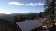 Timelapse mountain top view with snow covered house below from a mega deck. video