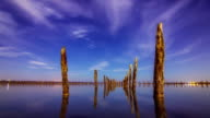Timelapse of a starry sky and clouds with wooden pillars and water in the foreground video