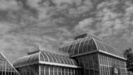 Time-lapse of clouds above green-house, black-white color video