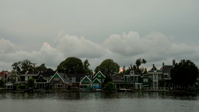 Timelapse of clouds over houses on river bank, Netherlands video