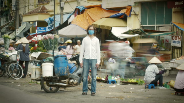 Time-lapse of man standing still at a busy market as the world whizzes by him video