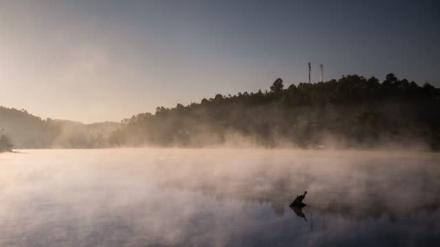 Time-lapse of moving mist on the Reflection lake with sunrise in the morning , 4k (UHD) video