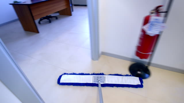 Timelapse of professional cleaner wiping floor with broom in office video