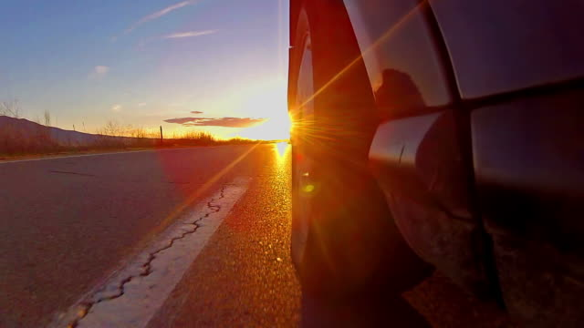 Timelapse of sport car driving toward sun rays at sunset video