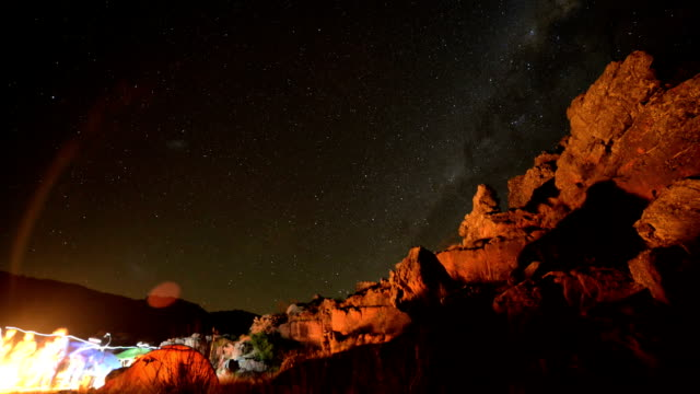 Timelapse of stars moving over mountain top, night time, from campsite video