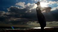 Timelapse of strong woman alone on seashore, female silhouette, dark video