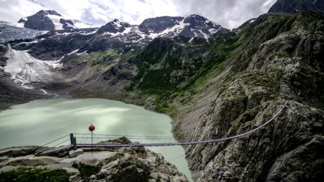 Time-lapse of suspension bridge over a glacier lake. video