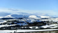 Timelapse rural winter scene with snow covered hills and fields video