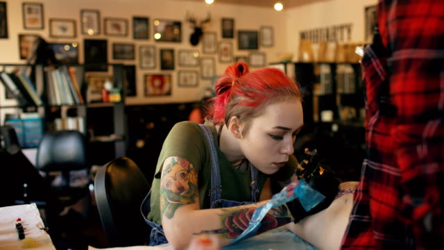 Timelapse speeded shoot of young tattoo artist girl tattooing on client's leg with concentrated expression video