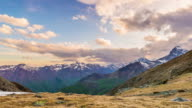 Timelapse view of snowcapped mountain ridges and peaks with moving clouds at sunset. The Alps, Torino Province, Italy. video