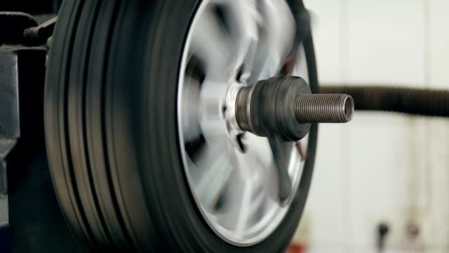 Tire service. Mechanic balancing a car wheel on automated machine. video