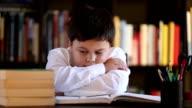 tired boy sleeping during his studies video