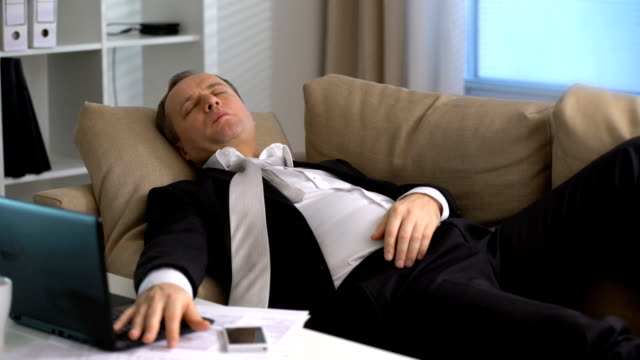 Tired businessman is sleeping on the sofa at the office video