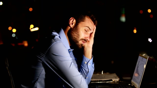 Tired businessman using laptop at night video