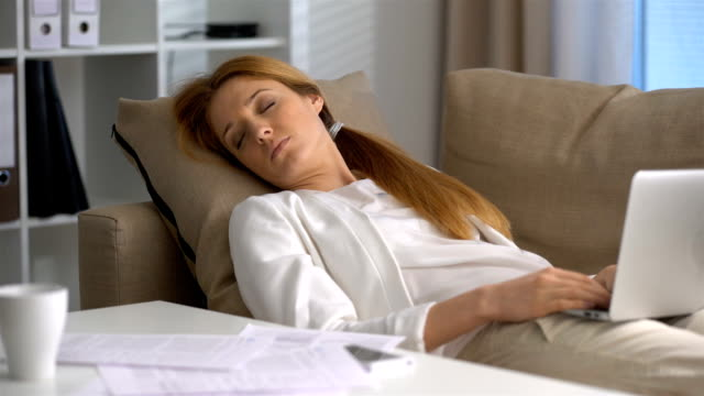 Tired businesswoman sleeping on the couch in the office with laptop and phone video