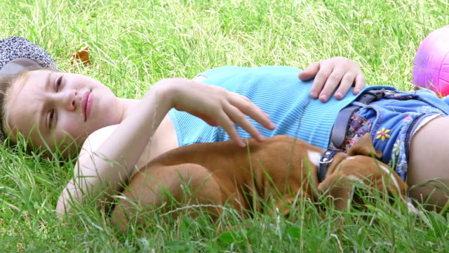Tired child with puppy relaxing on grass in summer garden video