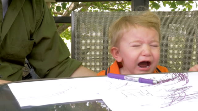 A tired crying toddler sitting at a table coloring video