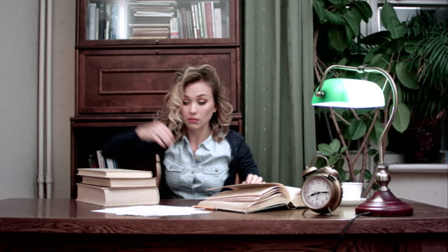 Tired female taking a nap on pile of books at her workplace and being woken up by an alarm video