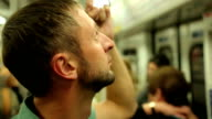 Tired male passenger reading advertisements inside subway train during rush video