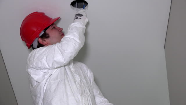 Tired male worker with red helmet cutting holes in ceiling video