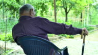 tired man sitting alone with hand leaned on a walking stick: elderly, senior video