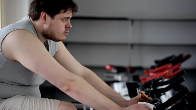 Tired man with an angry expression on his face eating pizza, engaging on an exercise bike video