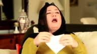 Tired, sick muslim woman sneezing video