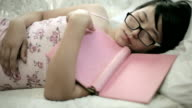 Tired student, Asian girl sleeping with book and eyeglasses on. video