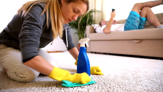 Tired wife cleans carpet while her husband lies on the couch with the phone video