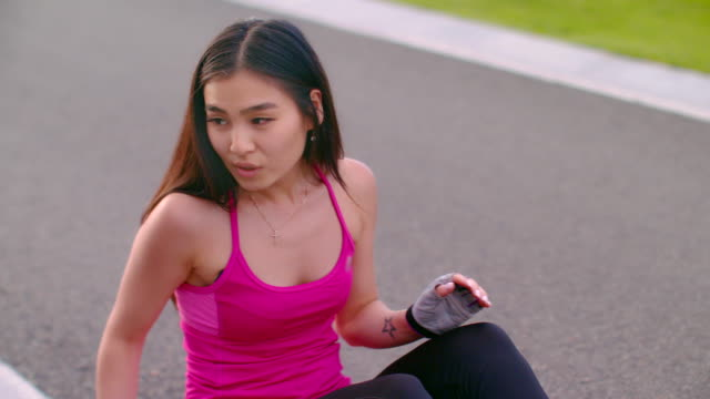Tired woman sitting on road. Exhausted woman breathing after running exercise video