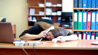 Tired woman sleeping on keyboard at work video