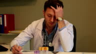 Tired young doctor working with stress video