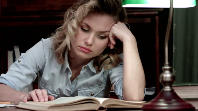 Tired young woman falling asleep over a book while sitting at the table after long day of work video