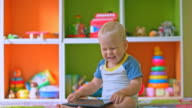 Toddler boy laughs playing with tablet computer video