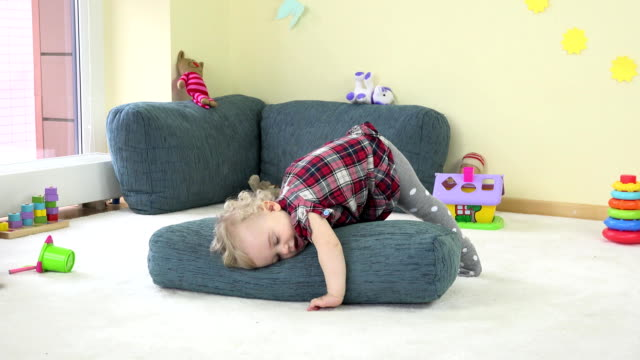 toddler child play with blue big pillow and show true emotions. video