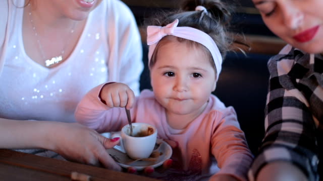 Toddler girl eating foam from coffee video