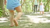 Toddler girls playing together, walking barefoot at park with mom video