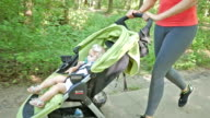 Toddler riding in jogging stroller as mom goes for run in park video
