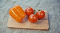 tomatoes, bell pepper lying on a wooden Board. Dolly shot video