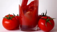 Tomatoes with leaves and tomato juice being poured into glass. Super slow motion video