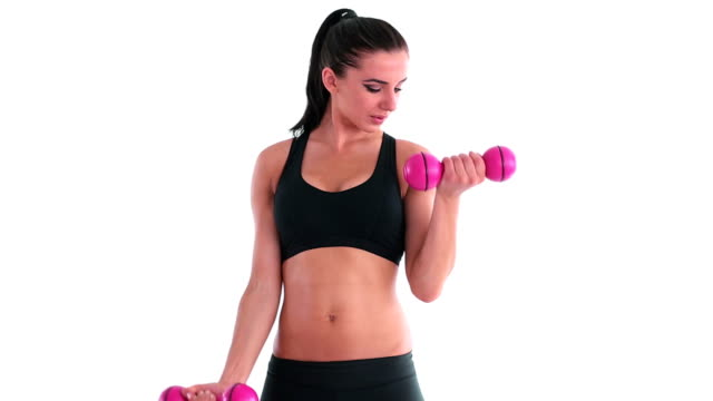 Toned smiling brunette working out with dumbbells video