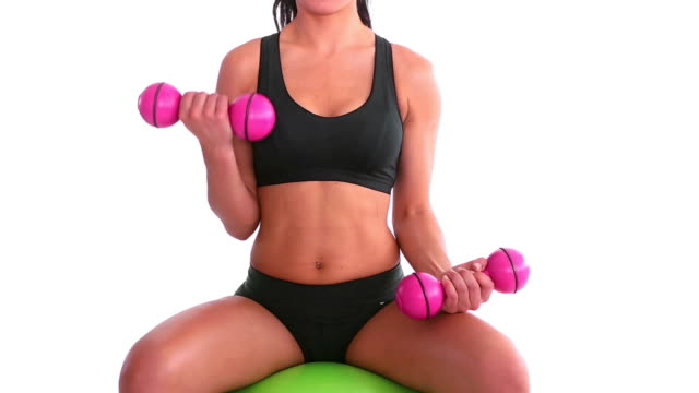 Toned woman sitting on exercise ball training with dumbbells video