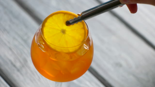 Tongs put orange into cocktail. video