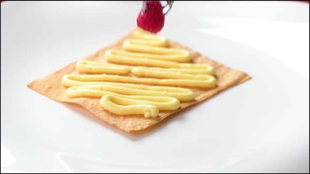 Tongs put raspberry on cream. video