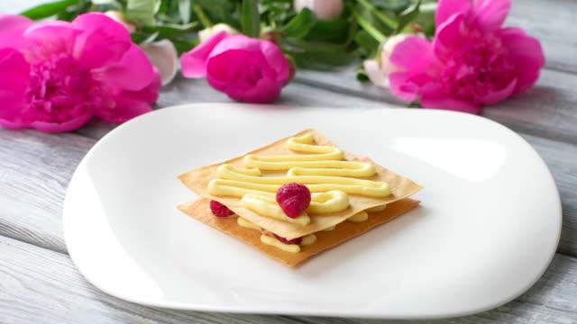 Tongs put raspberry onto cream. video