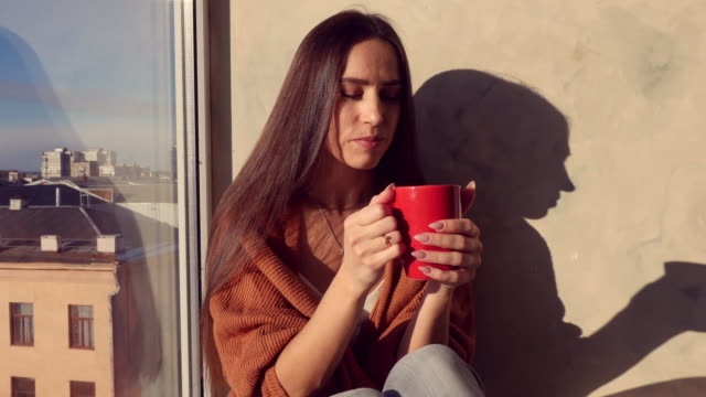Toothy smiling and fully rested female relaxing while drinking a cup of aroma coffee in the morning video