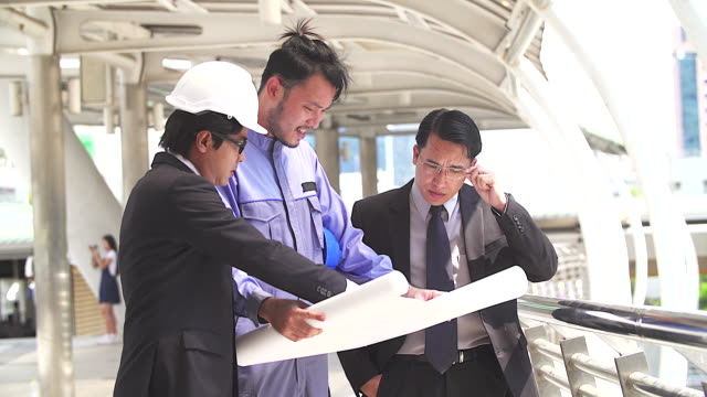 Top management with his engineers meeting at terrace on top of construction site. Coworkers discussing. Boss and worker argue. Conversation in team.wear helmet hold paper plans video