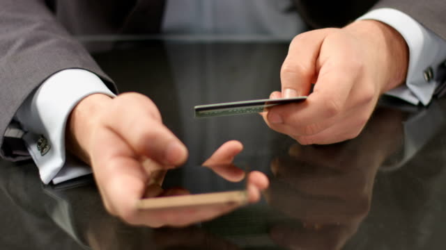 Top manager hands typing credit card number on smart phone video