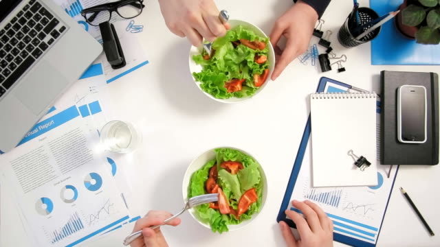Top view businessmen sitting at office desk and having a business lunch eating salad video
