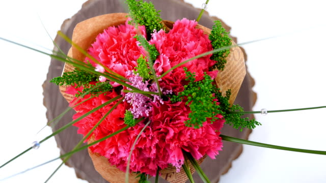 Top view, close-up of a bouquet of flowers, rotation on a white background. The flower arrangement consists of Carnation, Barbatus video